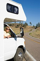Woman leaning out of window of motor home, smiling, portrait