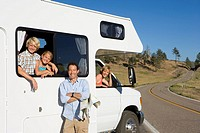 Family of four with motor home, man with map by son and daughter 8-12, mother looking out of window, smiling, portrait