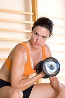 Woman using dumbbell, portrait, close-up