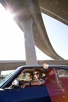 Two young men wearing sunglasses in car beneath overpass, smiling lens flare