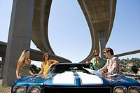Two young couples by car beneath overpass, low angle view