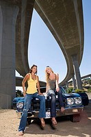 Two young women on bonnet of car beneath underpass, low angle view