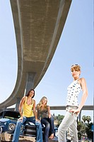 Small group of young women by car beneath overpass, portrait, low angle view