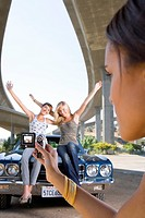 Young woman taking photograph of friends on bonnet of car beneath overpass, close-up (thumbnail)