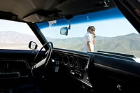 Young man in sunglasses using mobile phone by car in desert, view through windscreen of car