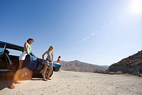 Small group of friends by car in desert, looking at view, low angle view lens flare