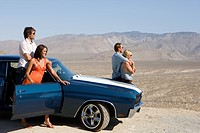 Two couples by car in desert, looking at view, side view