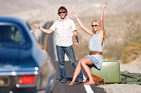 Young couple hitchhiking on desert road, car approaching, woman with arms raised
