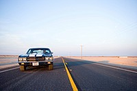 Classic car on freeway in desert, low angle view