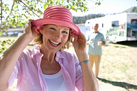 Mature woman with hat by husband and motor home outdoors, smiling, portrait, close-up