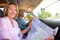 Mature woman with map in motor home with husband, smiling, portrait