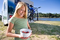 Girl 8-10 with bowl of strawberries by motor home and lake, smiling, portrait