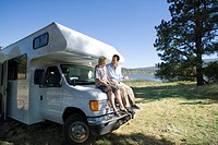 Father and son 10-12 smiling at each other on front of motor home by lake (thumbnail)
