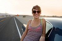Young woman in sunglasses by car on open road, smiling, portrait