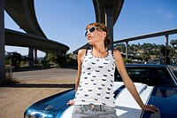 Young woman on bonnet of car beneath overpass, low angle view