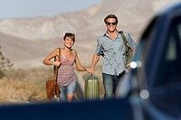 Young couple hitchhiking on open road, walking towards car, smiling, portrait