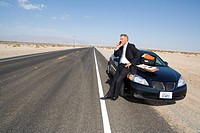 Businessman using mobile phone by car on side of road in desert, paperwork on bonnet of car