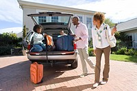 Parents smiling at children 8-10 siiting in boot of car with suitcases