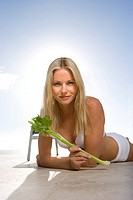 Young woman in swimsuit lying on stomach with celery, smiling, portrait
