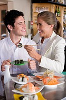 Young couple smiling at each other in Japanese restaurant, woman with chopsticks