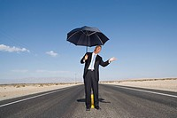 Businessman on open road in desert with umbrella, feeling for rain, low angle view