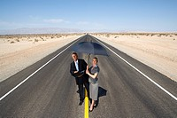Businessman and woman on open road in desert, man with laptop computer, woman with umbrella, elevated view