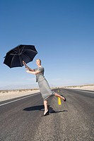 Businesswoman on open road in desert with wind blowing umbrella, low angle view