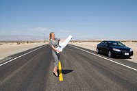 Businesswoman in middle of open road in desert with road map by car, low angle view