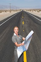 Businesswoman in middle of open road in desert with road map, portrait, elevated view