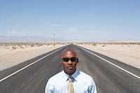 Businessman in sunglasses in middle of road in desert, elevated view (thumbnail)