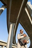 Businessman embracing briefcase beneath overpasses, low angle view