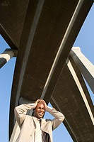 Businessman with hands to head beneath overpasses, low angle view