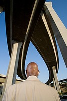 Businessman beneath overpasses, rear view