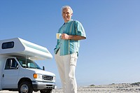 Mature man with mug by motor home on beach, smiling, portrait, low angle view (thumbnail)