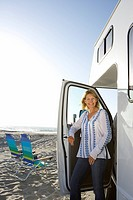 Mature woman getting out of motor home on beach, smiling, portrait