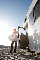 Mature woman with map by motor home on beach, low angle view lens flare