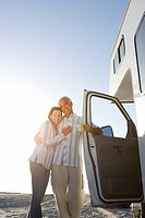 Mature couple arm in arm by motor home on beach, smiling, low angle view sun flare