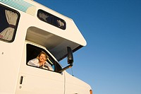 Mature woman looking out window of motor home, smiling, portrait, low angle view