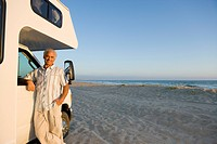 Mature man by motor home on beach, arm on window, portrait, low angle view