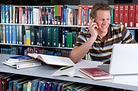 Young man studying in library, smiling, close-up