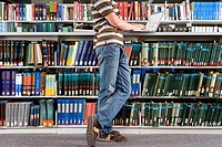 Young man studying in library, side view low section