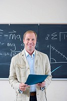 Male teacher with folder by blackboard in classroom, smiling, portrait