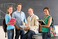 Male teacher sitting on desk in classroom surrounded by students, smiling, portrait