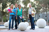 Teenage school students 16-18 and male teacher outdoors by concrete balls