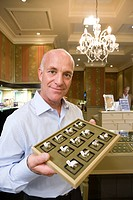 Mature male jewellery shop assistant with tray of rings, smiling, portrait (thumbnail)