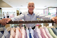 Mature man with hands on rail of shirts in shop, smiling, portrait