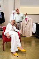 Mature man and woman in shop, woman in armchair, man with suit jacket, portrait