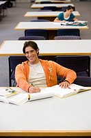 Young man studying in library, smiling, portrait, elevated view