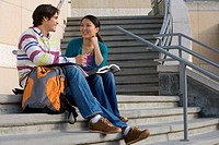 Young couple studying on steps, smiling at each other, low angle view