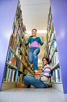 Young woman jumping over young man sitting on floor in library, low angle view